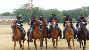 Image of men on horseback in 19th century U.S. Army cavalry uniforms.