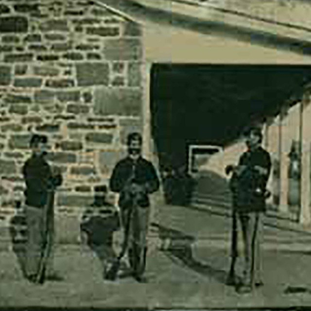 Historic image of 3 soldiers standing at the end of a sandstone building.