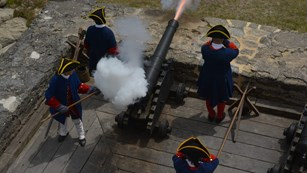 Cannon being fired surrounded by four soldiers.