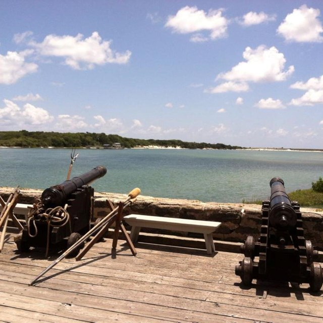 Two cannons on gun deck of the fort with river in background.