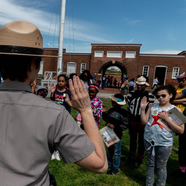 An image of a park ranger swearing in a group of junior rangers.