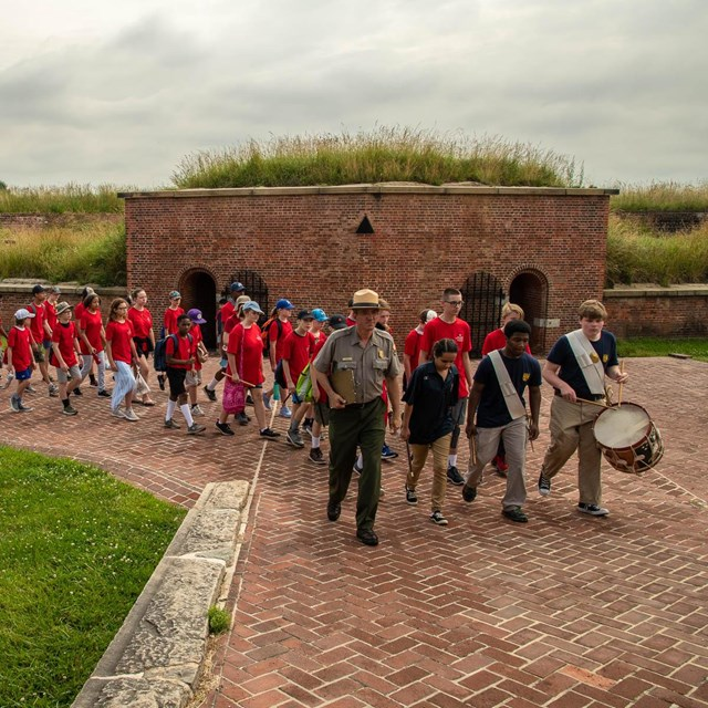 A park ranger leading a group of kids during Fort McHenry band camp.