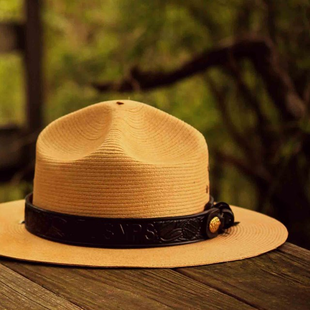 A summer park ranger hat on a wooden table.