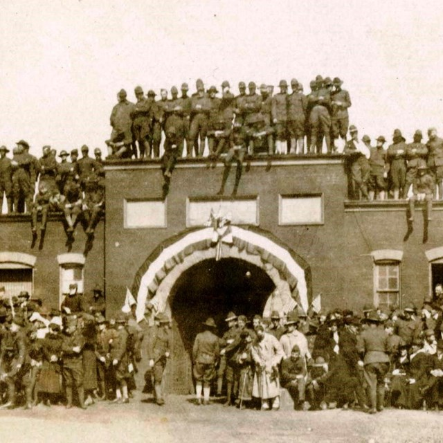 A black and white photograph showing a crowd of World War I soldiers on, and around, the sally port.