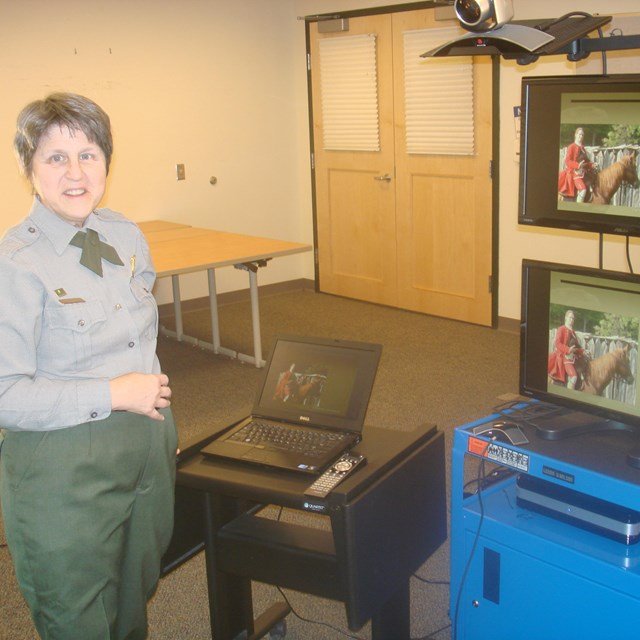 A park ranger in front of video conferencing equipment