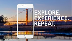 Image of cell phone with Golden Gate Bridge behind and text reading Explore. Experience. Repeat