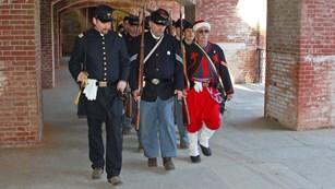 Civil War re-enacters walking through casemates at the fort