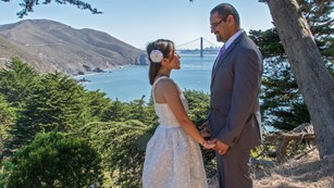 A couple in wedding attire with the Golden Gate Bridge behind