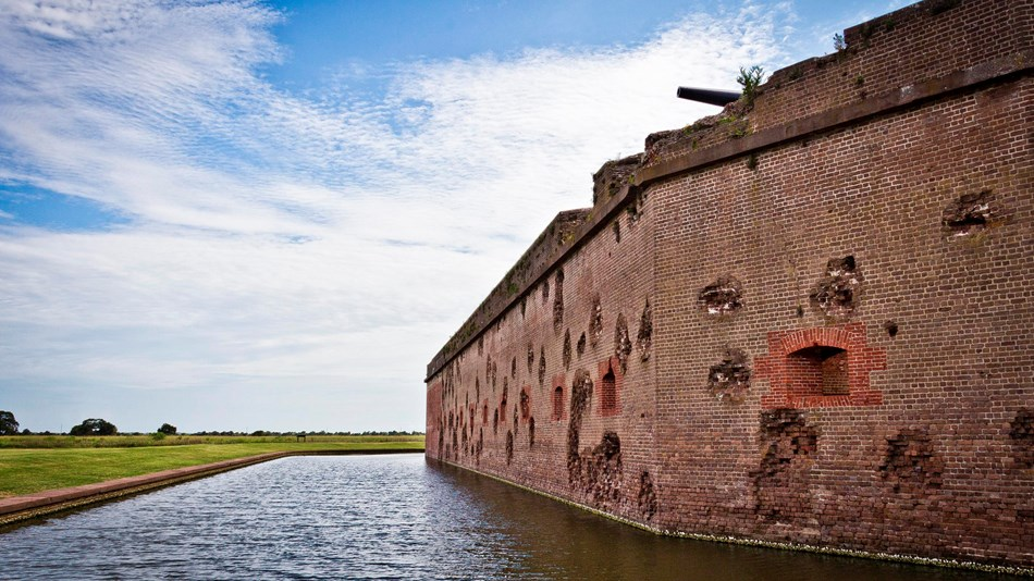 The outside wall of Fort Pulaski with battle scars, cannon, and moat.