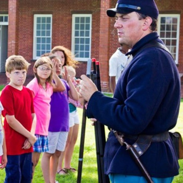 kid with civil war uniform standing with other kids, adult man in civil war uniform