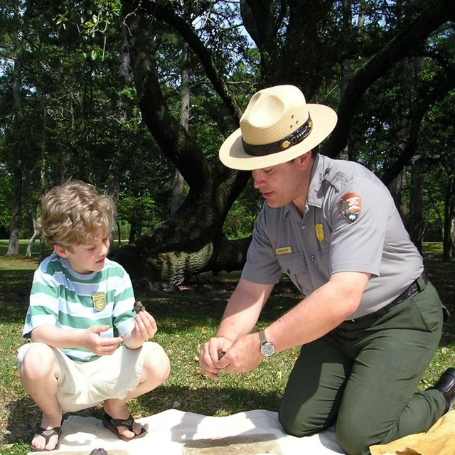 color photo of a ranger at left kneeling showing tree bark to a young boy sitting right