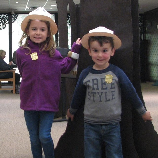 color photo of a young girl and boy standing in a museum wearing paper ranger hats with badges p