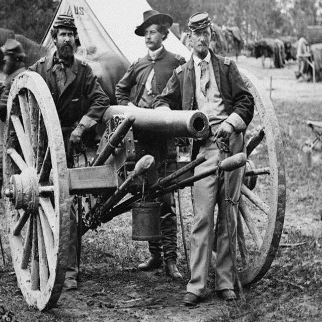 black and white photo of four civil war soldiers standing behind a cannon