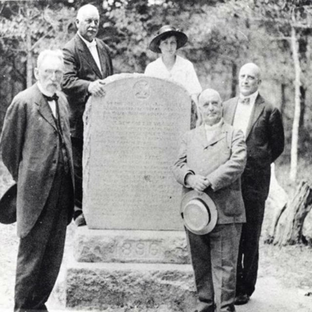 black and white photo of a stone marker with 4 men and 1 woman standing to the side