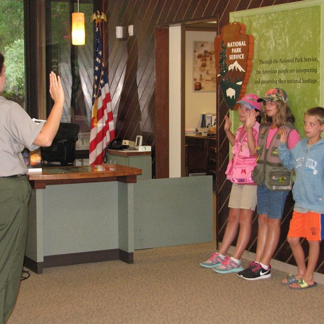 color photo of a ranger standing left swearing in three Junior Rangers standing right