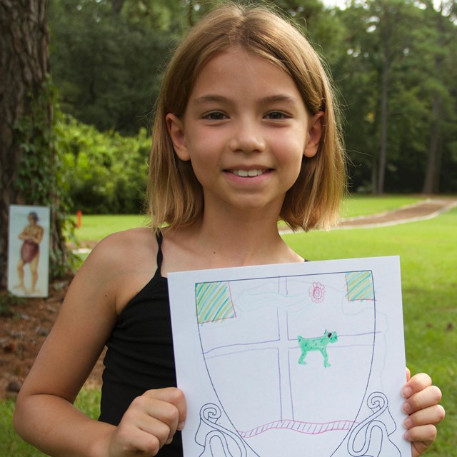 Child with coat of arms drawing