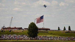 fighter jets fly over a fort with crowd below