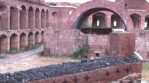 inside a brick fort with archways on the left and bin of coal in foreground