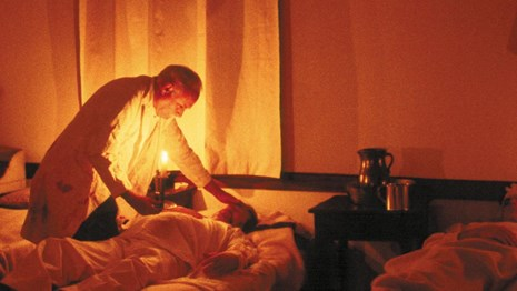 Surgeon treating a patient in a hospital bed