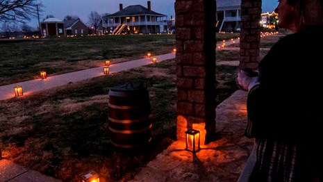 Lady looks out over parade ground lined with candle lanterns