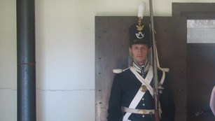Soldier in dress clothing with tall shako