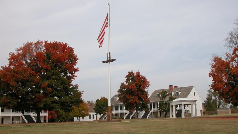 The grassy parade ground with the american flag on a 60 foot tall flag pole and officer's quarters.