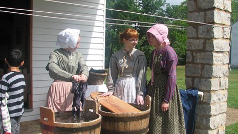 Three laundresses doing laundry while a student looks on.
