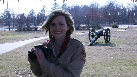 Feamal park volunteer holding a camera with a cannon in the background