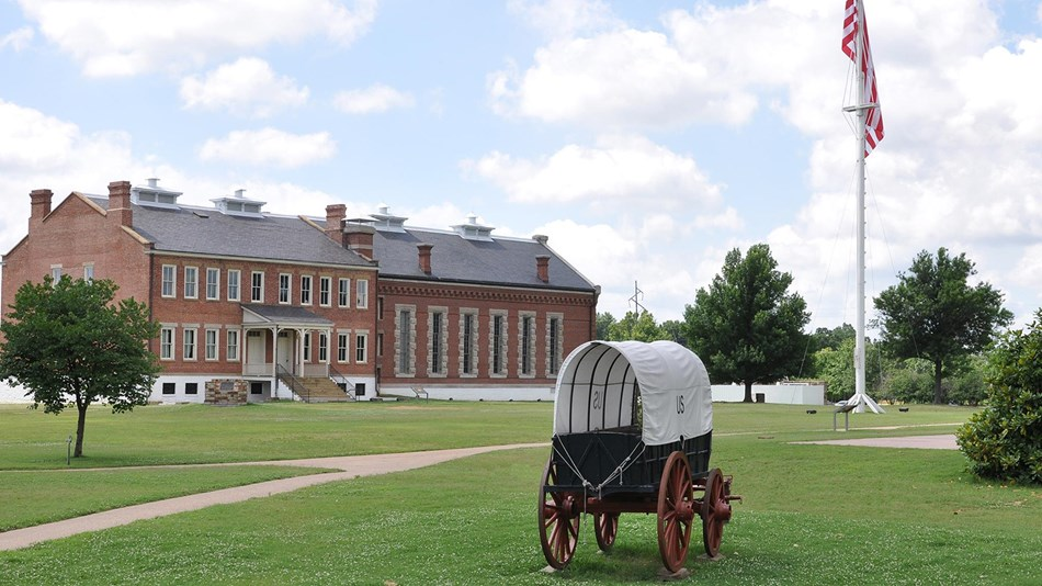 Supply wagon in front of grass parade ground, flagpole and red brick visitor center.