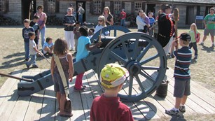 Children stand around a cannon holding different tools.