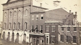 1865 black & white photo of Ford's Theatre and nearby buildings draped in mourning banners.