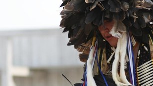 Profile portrait of man, wearing feather headdress, holding feather fan.