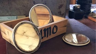 Wooden box reads U.M.O, three small round mirrors placed around with FUA Logo in foreground
