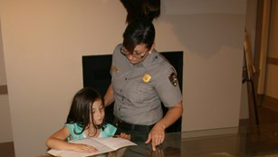 Park Ranger points out items in museum display case to two Jr. Rangers