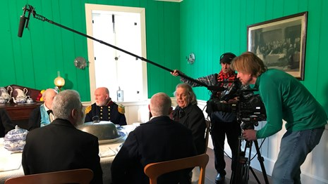 A camera crew films a group of men sitting at the Chief Factor's House table.