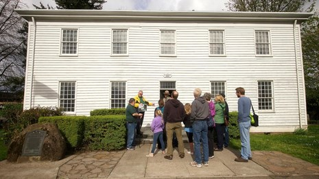 A large tour group led by a docent stands in front of the McLoughlin House.