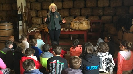 A volunteer talking to a school group in the Fort Vancouver Fur Store.