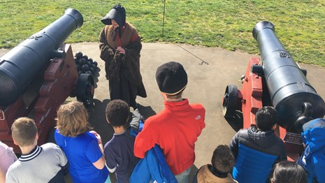 A woman in 1840s clothing talking to a group of students at Fort Vancouver.