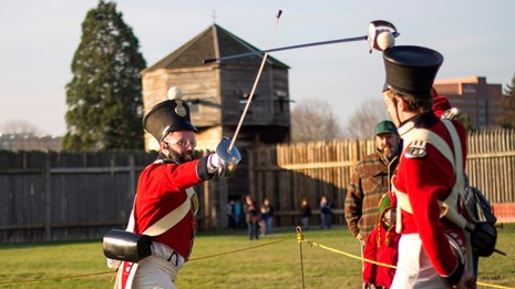 Photo of two reenactors wearing military uniforms and drilling with sabers