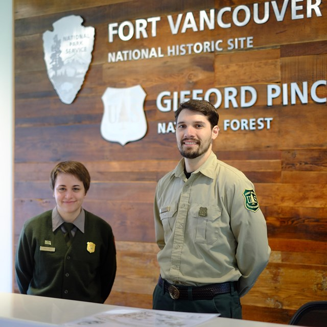 A national park ranger and a forest ranger inside the Fort Vancouver Visitor Center.
