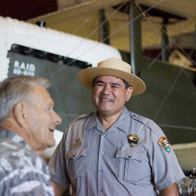 A park ranger stands in front of an aircraft at Pearson Air Museum.