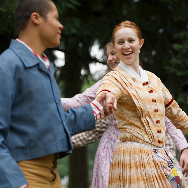 Costumed 19th century re-enactors demonstrate a historic dance