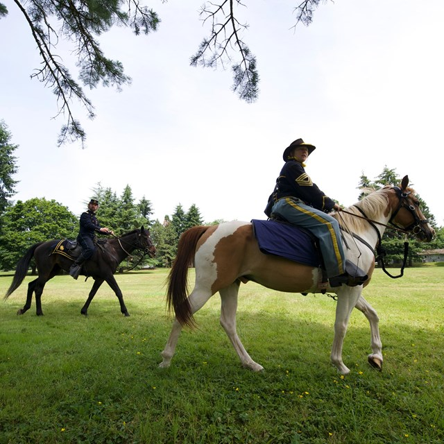Costumed re-enactors dressed as 19th century US Army soldiers ride horses at Fort Vancouver NHS