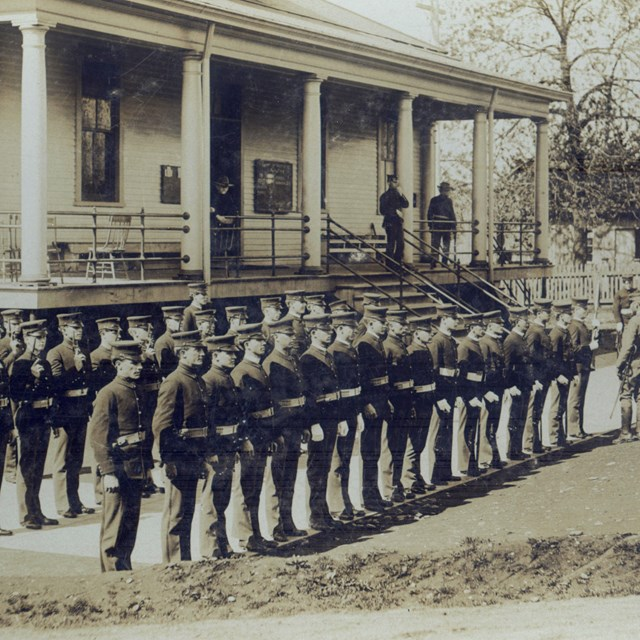 Historic photograph of soldiers standing in front of a building at Vancouver Barracks