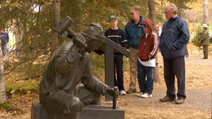Visitors standing behind a bronze statute of a settler using tools.