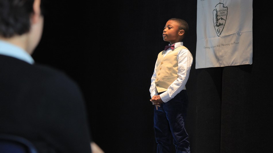A young student gives a speech from a stage
