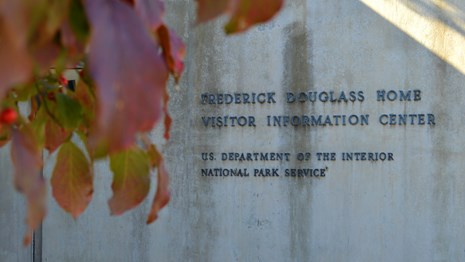 A sign for the Frederick Douglass National Historic Site visitor center with leaves in foreground