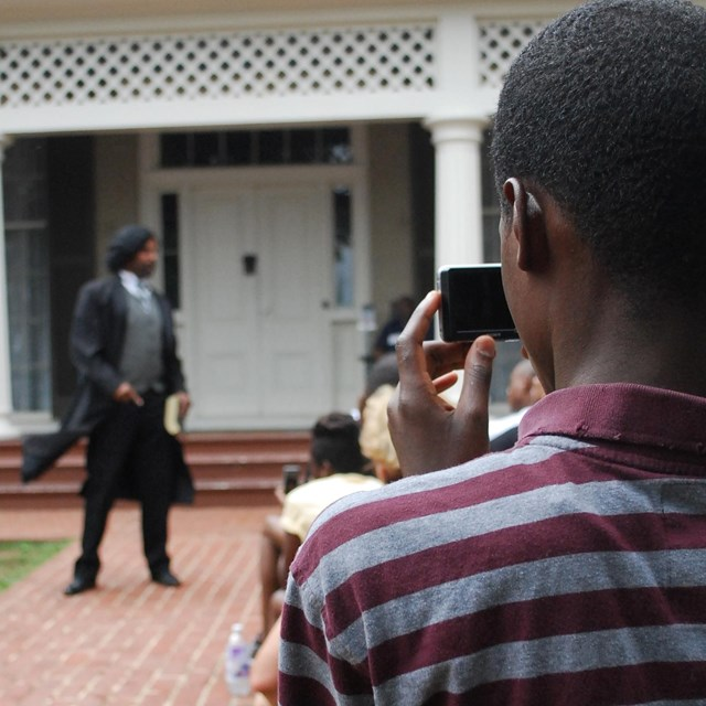 A young man takes a photograph of an actor portraying Frederick Douglass