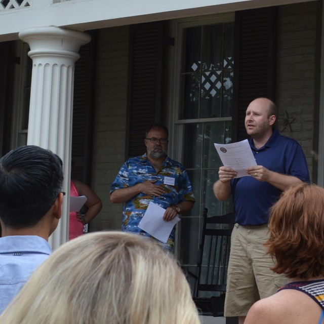 A man reads a speech from the front porch of a historic house