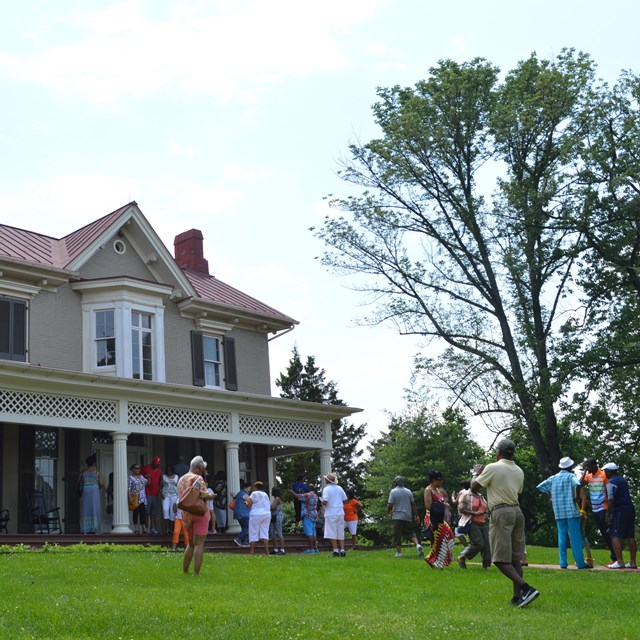 A group of visitors in front of a historic house
